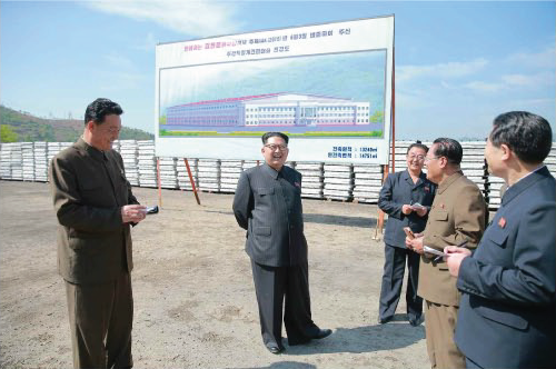 """Kim poses at the construction site of a """"modernizes steel casting workshop. (Image from Rodong Sinum showing Kim Jong Un's May 2016 visit.)"""