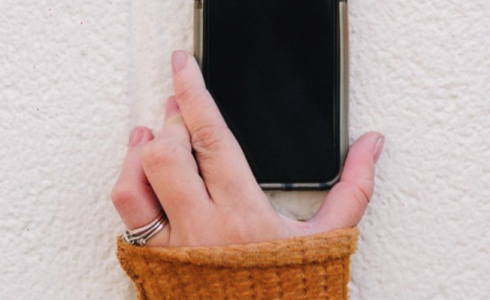 Caucasian hand holding iPhone against white background