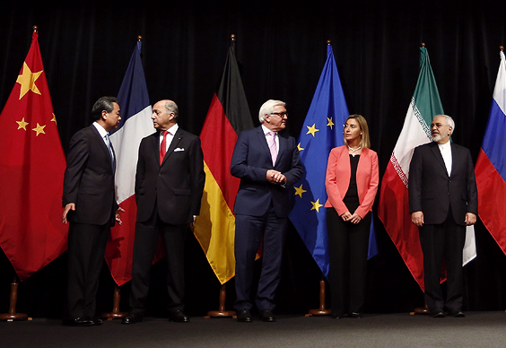 Government officials standing in front of their country's flags